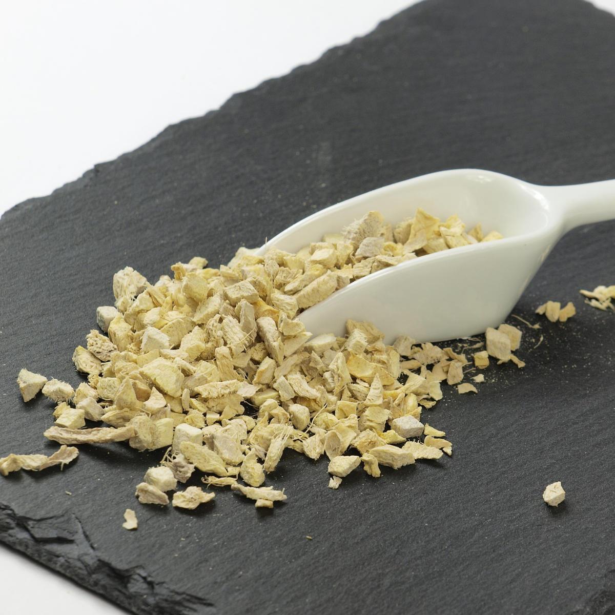 Colher de cerâmica com gengibre seco em pedaços pequenos em cima de lousa